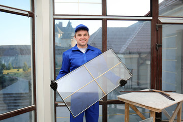 Fototapeta Construction worker holding window glass indoors obraz