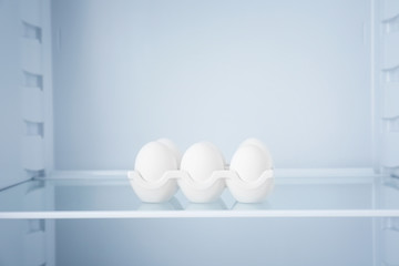 Raw eggs in empty refrigerator