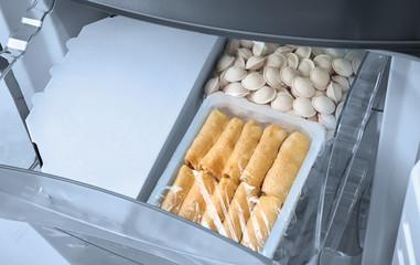 Frozen processed food in refrigerator icebox, closeup