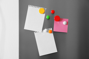 Blank paper sheets and magnets on refrigerator door