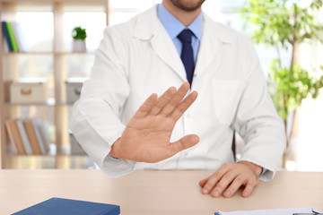 Male doctor refusing to take bribe at workplace