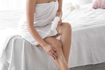 Woman applying body cream on her leg in bedroom, closeup
