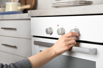 Young woman switching on modern electrical oven in kitchen