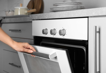 Young woman opening modern electrical oven in kitchen
