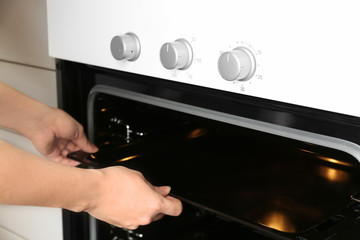 Young woman taking baking pan out of modern electrical oven in kitchen