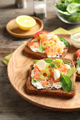 Tasty bruschettas with olives and salmon on wooden plate