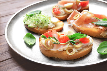 Tasty bruschettas with prosciutto and olives on plate