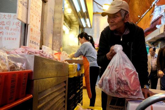 Cheung Muk-gun takes meat to a store at a street market at Mongkok district in Hong Kong