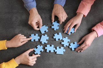 Group of people with puzzle pieces on gray background. Unity concept