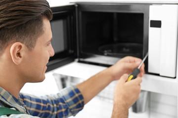 Young man repairing microwave oven, closeup