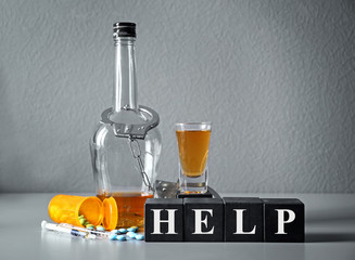 Strong drink, drugs, handcuffs and cubes with word HELP on table. Concept of alcoholism