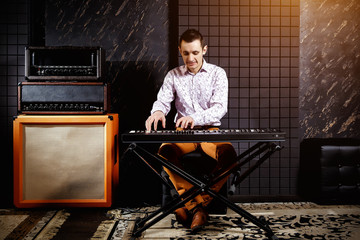 A musician in a light shirt plays a piano synthesizer in a dark recording studio.