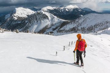 Mountaineer walking on the snowy slope of the Dovska Baba mountain in Karavanke range, Slovenia