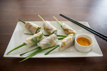 Fresh spring rolls Vietnamese lunch on wooden table. Asian food background.