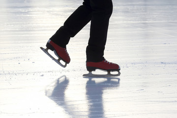 the legs of a man skating on the ice rink