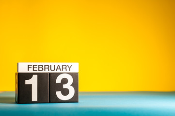 February 13th. Day 13 of february month, calendar on yellow background. Winter time. Empty space for text