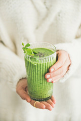 Healthy vegan breakfast. Matcha green smoothie with chia seeds and mint in hands of woman wearing white woolen sweater. Clean eating, vegetarian, alcaline diet, weight loss food concept