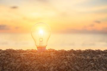 Clear light bulb on sunset beach, energy concept