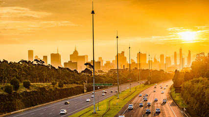 A view along the Eastern Freeway towards the cityscape of Melbourne, Australia during sunset.