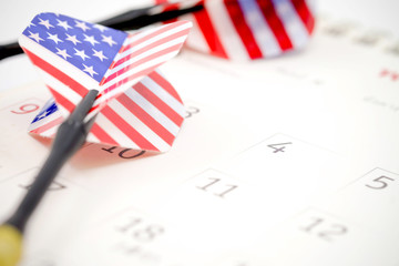 US flag darts on calendar background with selective focus 4th
