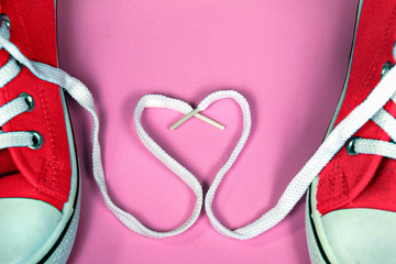 pair of bright red sneakers with heart shoelace on pink background