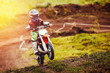 Racer child on motorcycle participates in motocross cross-country in flight, jumps and takes off on springboard against sky. Concept active extreme rest teenager.