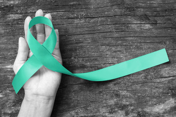 Mint green ribbon awareness for Genetic Disorder, Ivemark Syndrome, Congenital hepatic Fibrosis, and Autosomal Recessive Polycystic Kidney Disease with bow on helping hand support on aged wood