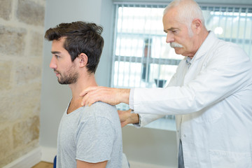 male chiropractor doing neck adjustment in a rehabilitation center