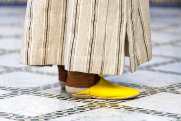 Man dressed in traditional moroccan dress and yellow shoes in Marrakech