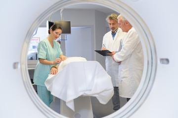 View of medical team through circular mri scanner
