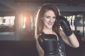 Young caucasian woman doing exercise with Thai boxing (Muay Thai) equipment in gym. Health and fitness concept.