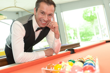 man posing on the billiard table