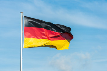 German flag waggling in the wind with sky in background