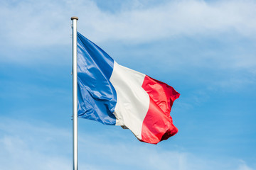 French flag waggling in the wind with sky in background