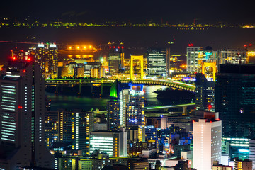 Asia Business concept for real estate & corporate construction - panoramic modern city skyline view of odaiba & rainbow bridge with neon night in Roppongi Hill, Tokyo, Japan