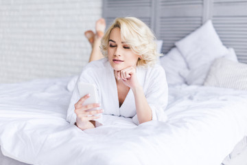 beautiful young woman in bathrobe using smartphone while lying on bed