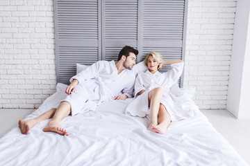 full length view of beautiful young couple in bathrobes lying together on bed