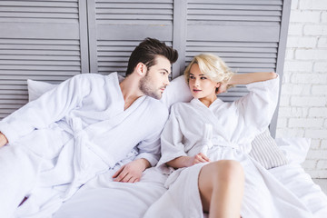 beautiful young couple in bathrobes looking at each other while lying together in bed