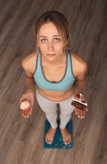 Dieting woman staying on scales and holding two cakes. Watching in the camera. View from above.