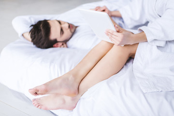 cropped shot of girl using digital tablet while boyfriend lying on bed