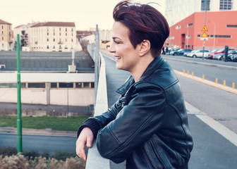 Beautiful and happy woman wearing leather jacket, windy day in the city