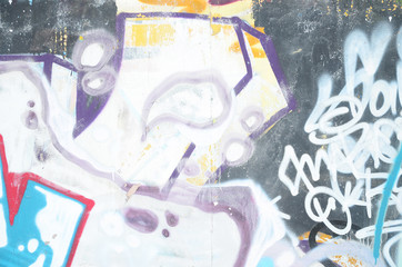 Close-up fragment of a graffiti drawing applied to the wall by aerosol paint. The wall is spoiled by a multitude of colorful signatures and tags from street artists and hooligans