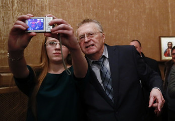 A student takes a selfie with leader of the Liberal Democratic Party of Russia and presidential candidate Zhirinovsky following his meeting with youth at the Tula State University in Tula