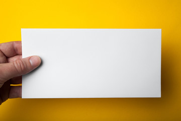 A man's hand holds a DL flyer on a yellow background.