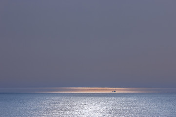 SEAS AND OCEANS - A small ship in space at sunset