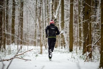 Image from back of man in sportswear, red cap on run in winter