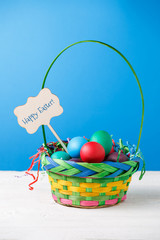 Image of basket with colorful eggs with wish for happy Easter