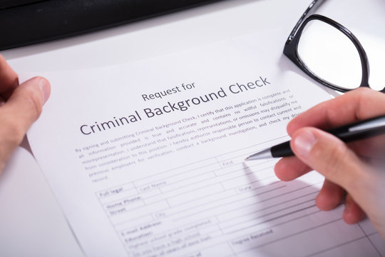 Person Hand Filling Criminal Background Check Application Form