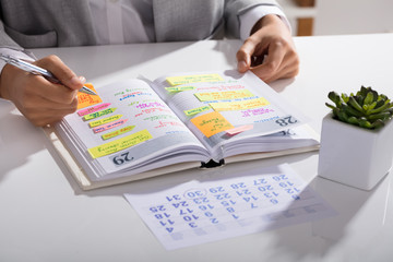 Fototapete - Businesswoman Making Agenda On Personal Organizer