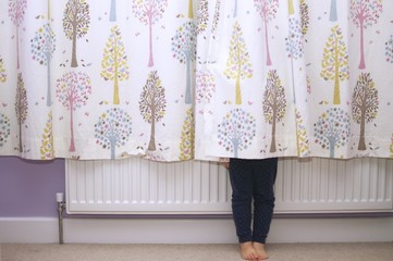 A young girl hiding behind curtains so that you can only see her legs